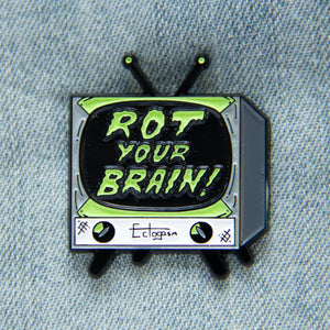 "A horror movie inspired enamel pin of a vintage TV set with the quote, ""Rot Your Brain"" in glow-in-the-dark letters."