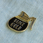 A gold enamel pin badge for baristas.