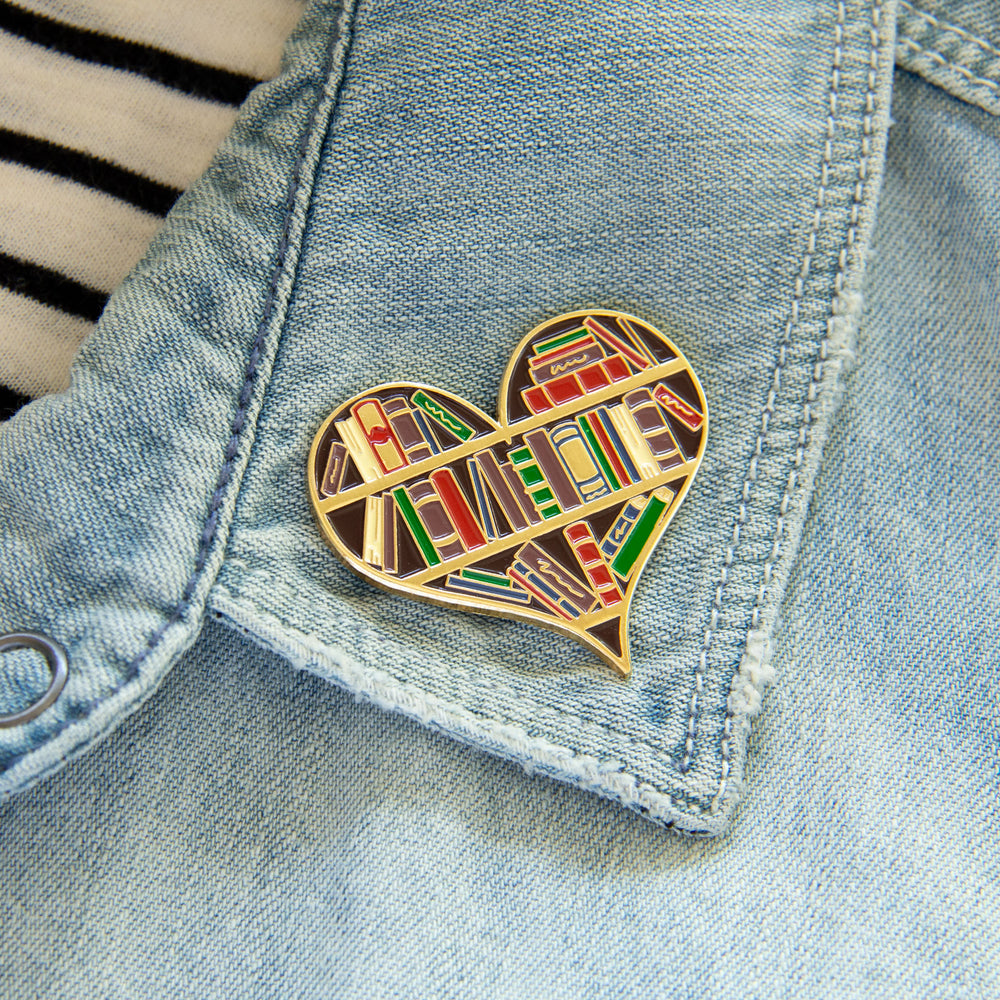 A large enamel pin of a bookshelf shaped like a heart.