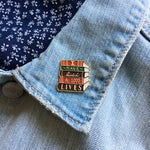 "A librarian style brooch of a stack of books with the quote, ""I Have Lived A 1,000 Lives"". Pinned on a denim jacket lapel."