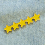 A five star rating enamel pin in gold and yellow.