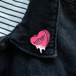 "A spooky Valentine's enamel pin of a heart with the word, ""succubus"" on it. Worn on the lapel of a women's jacket."