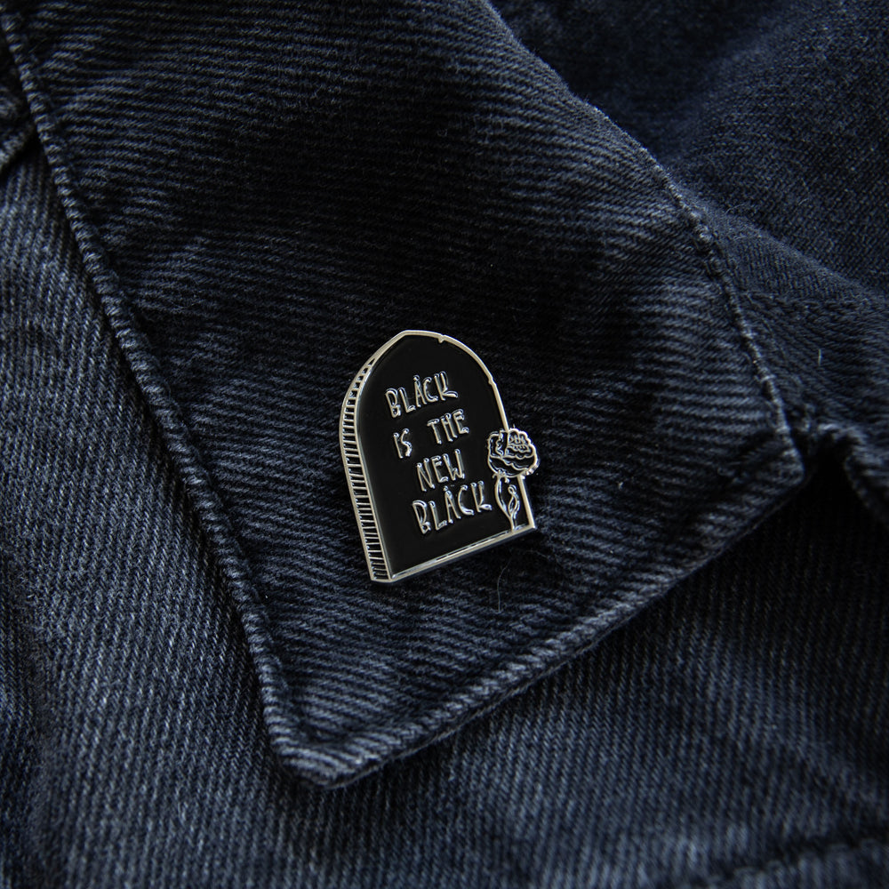 "Ectogasm's ""Black is the New Black"" silver gravestone quote enamel pin on the lapel of a black denim jacket for alternative fashion."