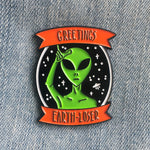 "A funny enamel pin of an alien giving the L sign. It is pictured on a galaxy background with a flying saucer. Two orange banners around the scene have the quote, ""Greetings, Earth-Loser""."