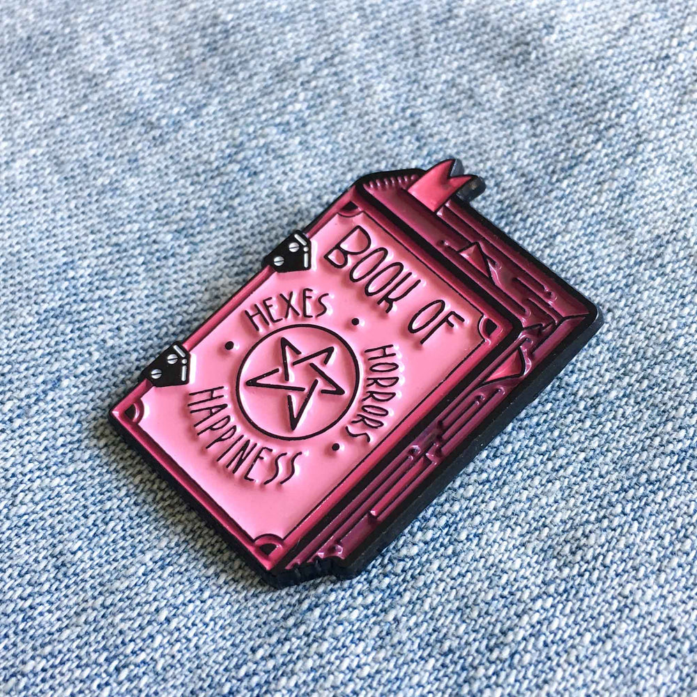 A pink enamel pin of a spell book with a funny title on the cover.