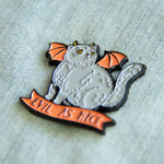 "A cute Halloween cat enamel pin with the funny quote, ""Evil as Heck""."