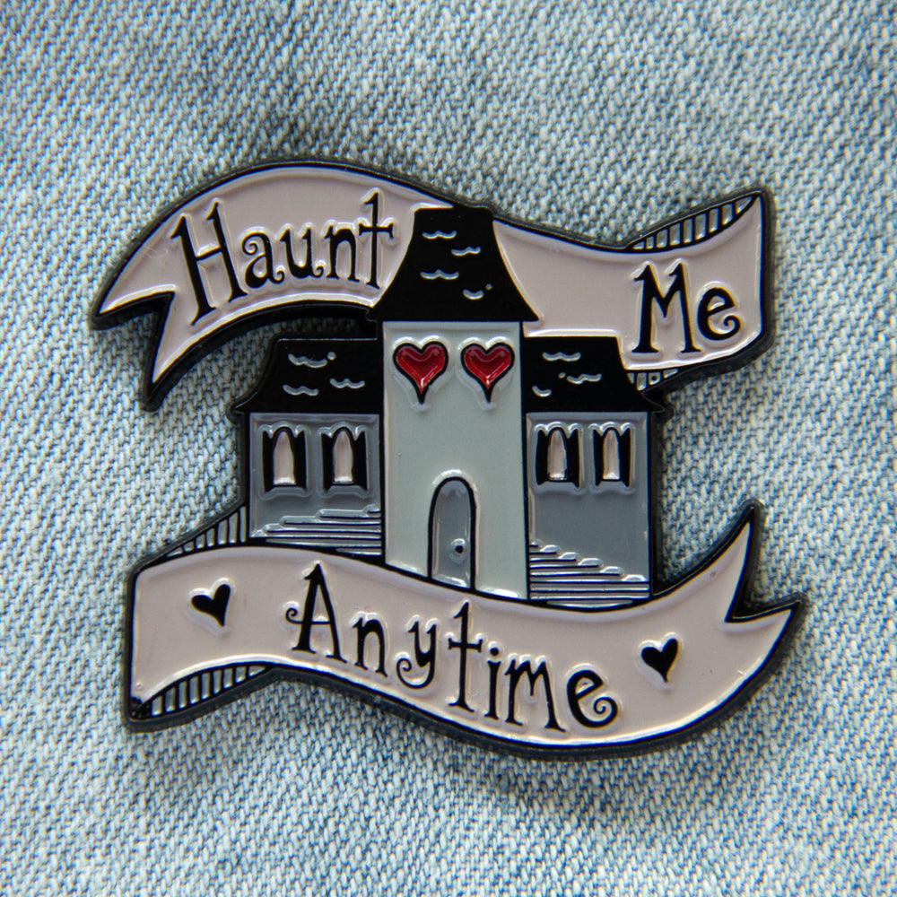 "Spooky haunted house enamel pin with the quote, ""Haunt me Anytime""."