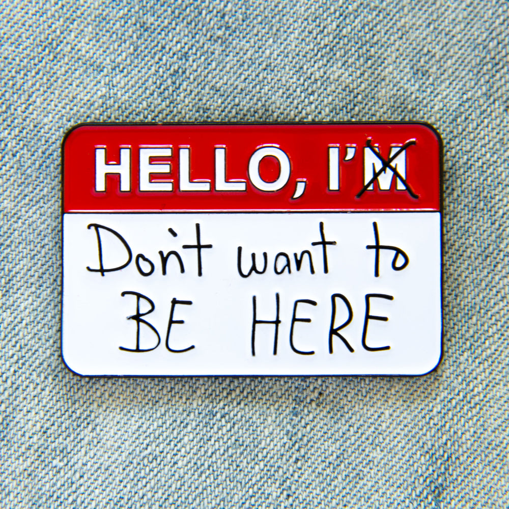 "A funny enamel pin of a ""Hello"" name tag with the quote, ""I don't want to be here""."