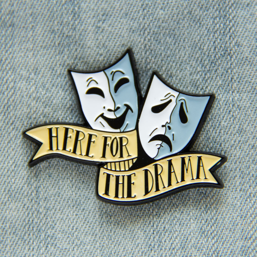 "A funny enamel pin of theater masks with the quote, ""Here for the Drama""."