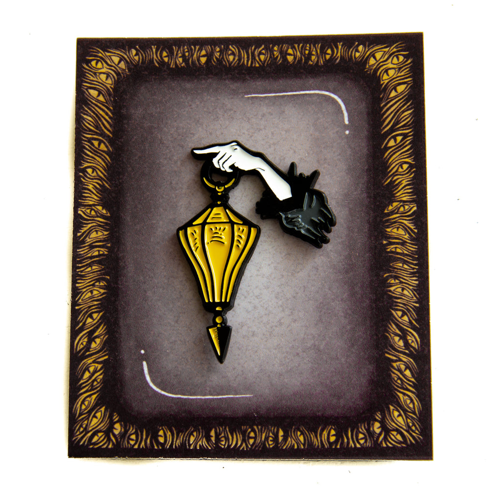 Spooky curio packaging on a black, white, and yellow lantern enamel pin.