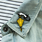 A horror themed enamel pin on the lapel of a denim jacket.