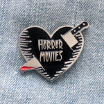 "A silver enamel pin of a black heart stabbed through with a bloody knife. Inside the heart is the phrase, ""Horror Movies""."