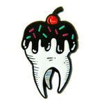 A creepy cute enamel pin of a tooth covered in chocolate and sprinkles for pastry chefs.