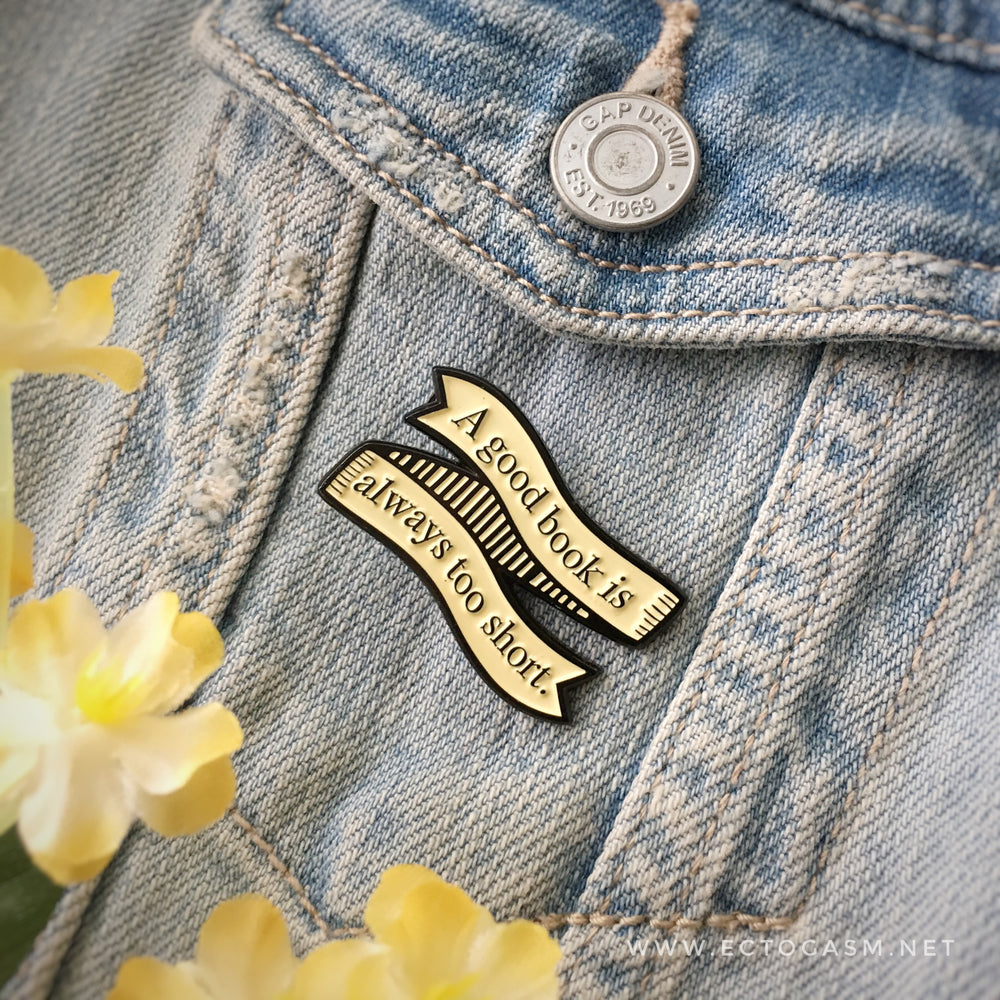 A book pin on a denim jacket for geek chic fashion.