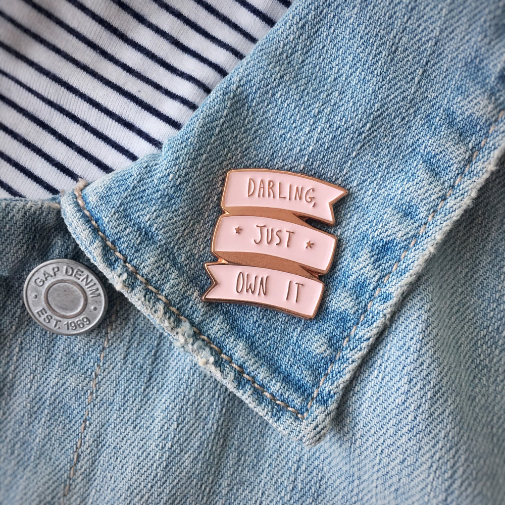 "Ectogasm's ""Darling Just Own It"" pink pin on a jacket lapel."