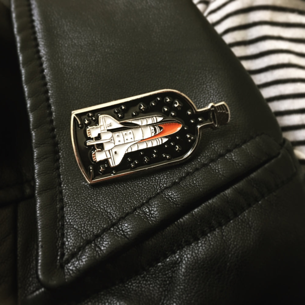 A cool enamel pin of a spaceship on a leather jacket lapel.