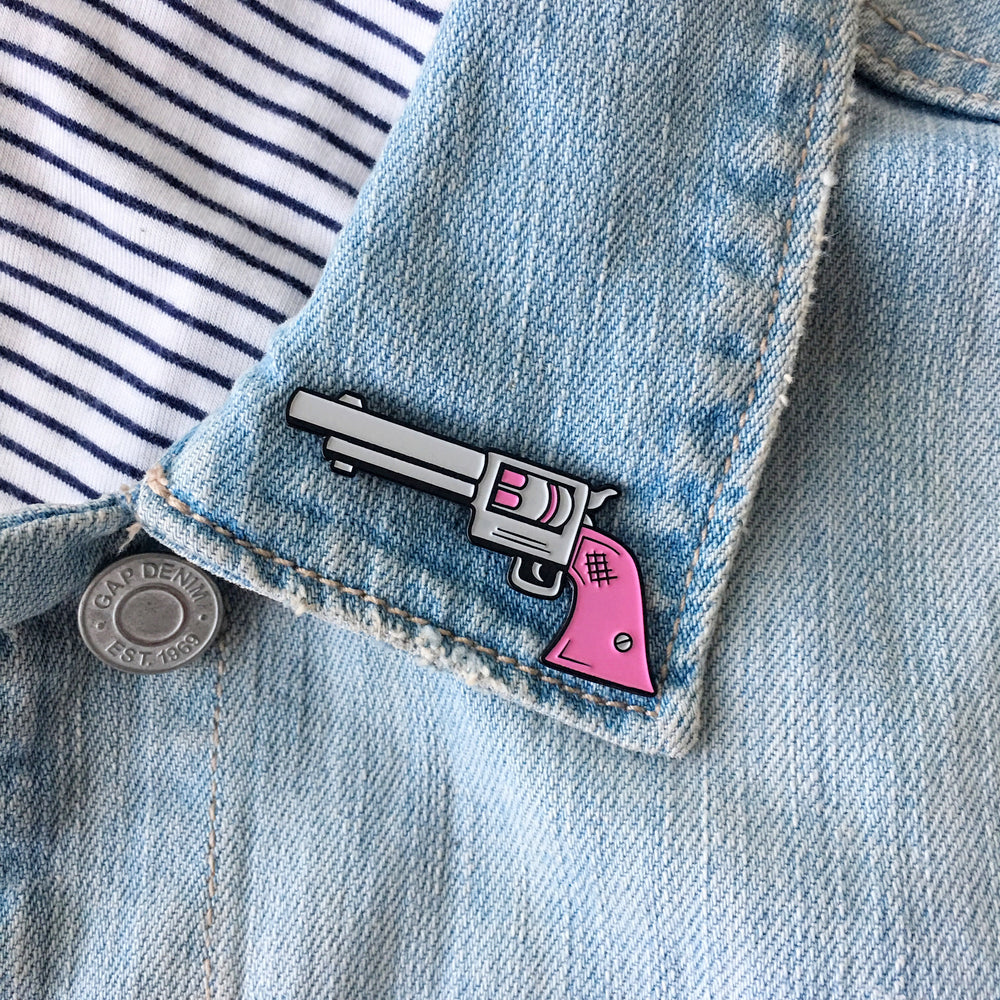 A pink gun pin on a jacket lapel.