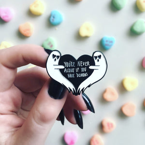 A funny, dark humor enamel pin of ghosts with a black heart.