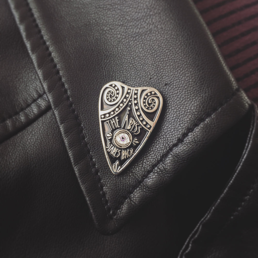 A black and silver tentacle plachette on the lapel of a leather jacket.