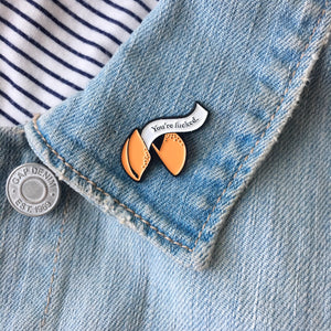 A funny fortune cookie enamel pin on a jacket lapel.