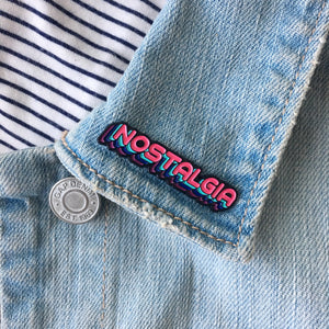 "Load image into Gallery viewer, A pink ""Nostalgia"" pin on a jacket lapel."