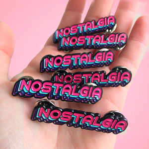 "A handful of hot pink, 80's themed enamel pins with the word, ""nostalgia""."