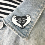 a funny ghost lapel pin on a denim jacket.