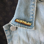 An orange nostalgia button on a jacket lapel.