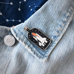 A futuristic pin of a rocketship in a bottle, pictured on a jacket lapel with a constallation scarf.