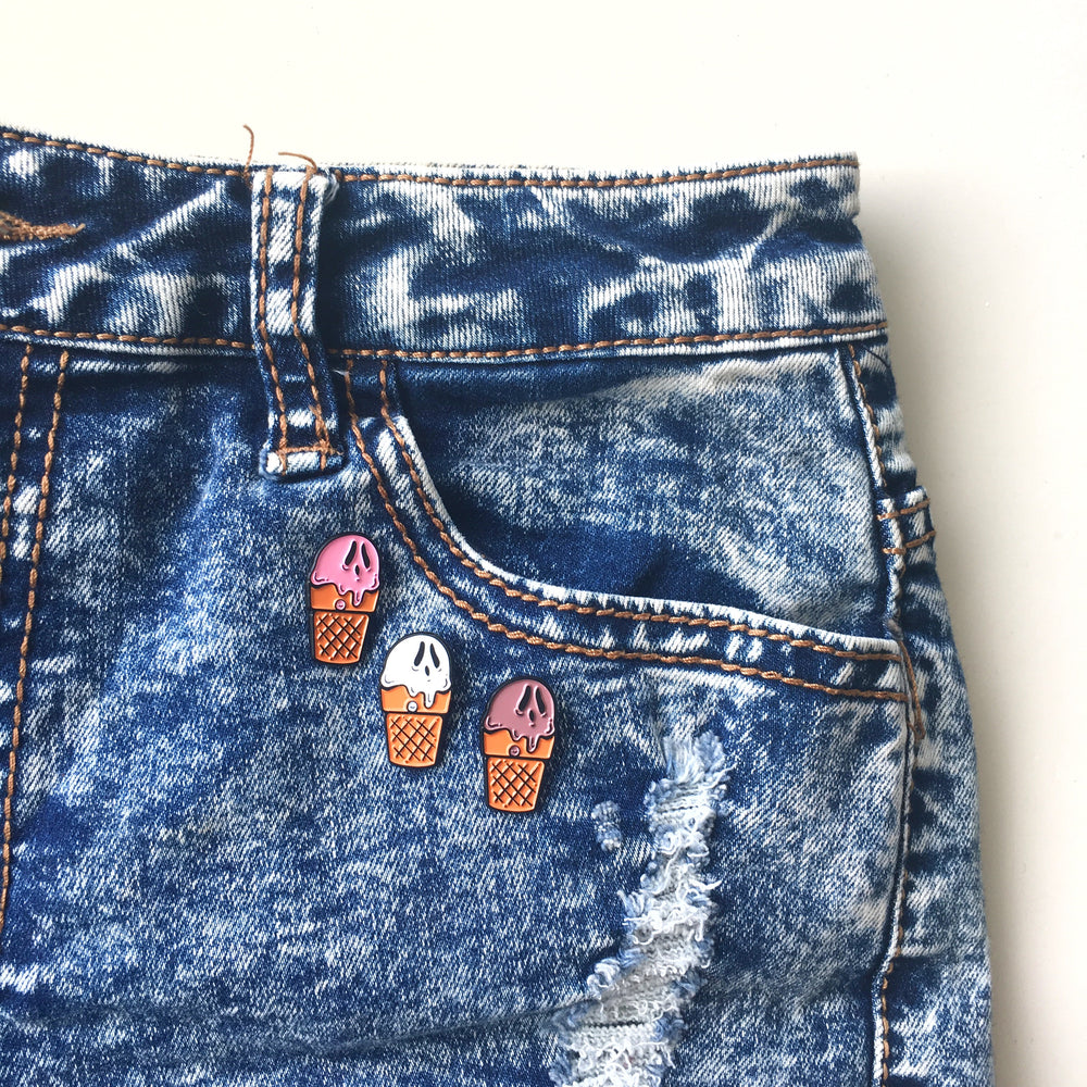 A cute collection of ghost enamel pins on a pair of high waisted shorts for summer goth fashion.
