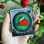 A christmas gag gift of a coal enamel pin.