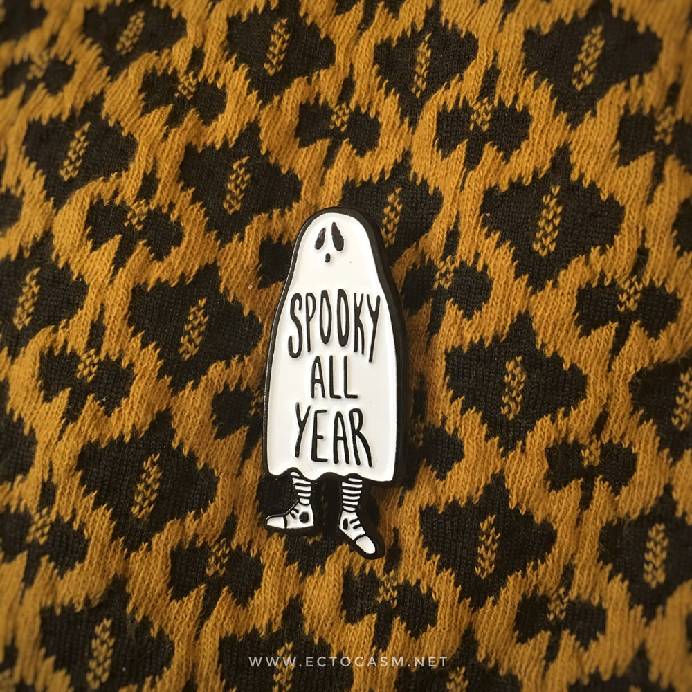 "An enamel pin of a ghost that says, ""Spooky All Year"" on a dress for witch fashion."