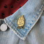 A campfire brooch shown on the lapel on a denim jacket.