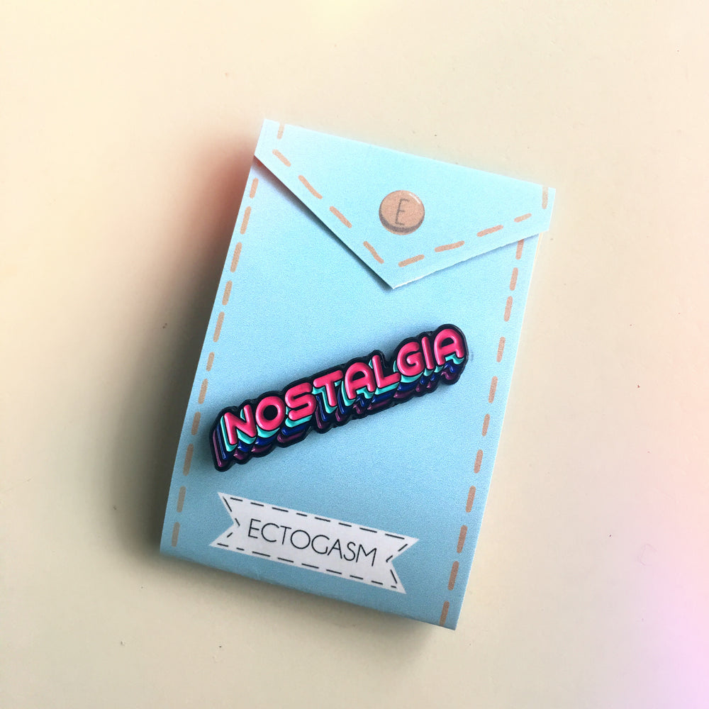 "A pink ""Nostalgia"" word lapel pin on its Ectogasm packaging card."