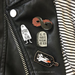 cool music lapel pins on a leather jacket.