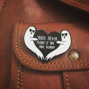 "a cool ghost enamel pin of a heart that says ""Youre never alone if you have demons"", shown on a cognac leather purse for fall fashion."