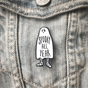"A ghost pin that says, ""Spooky All Year"" on a denim jacket for Halloween style."