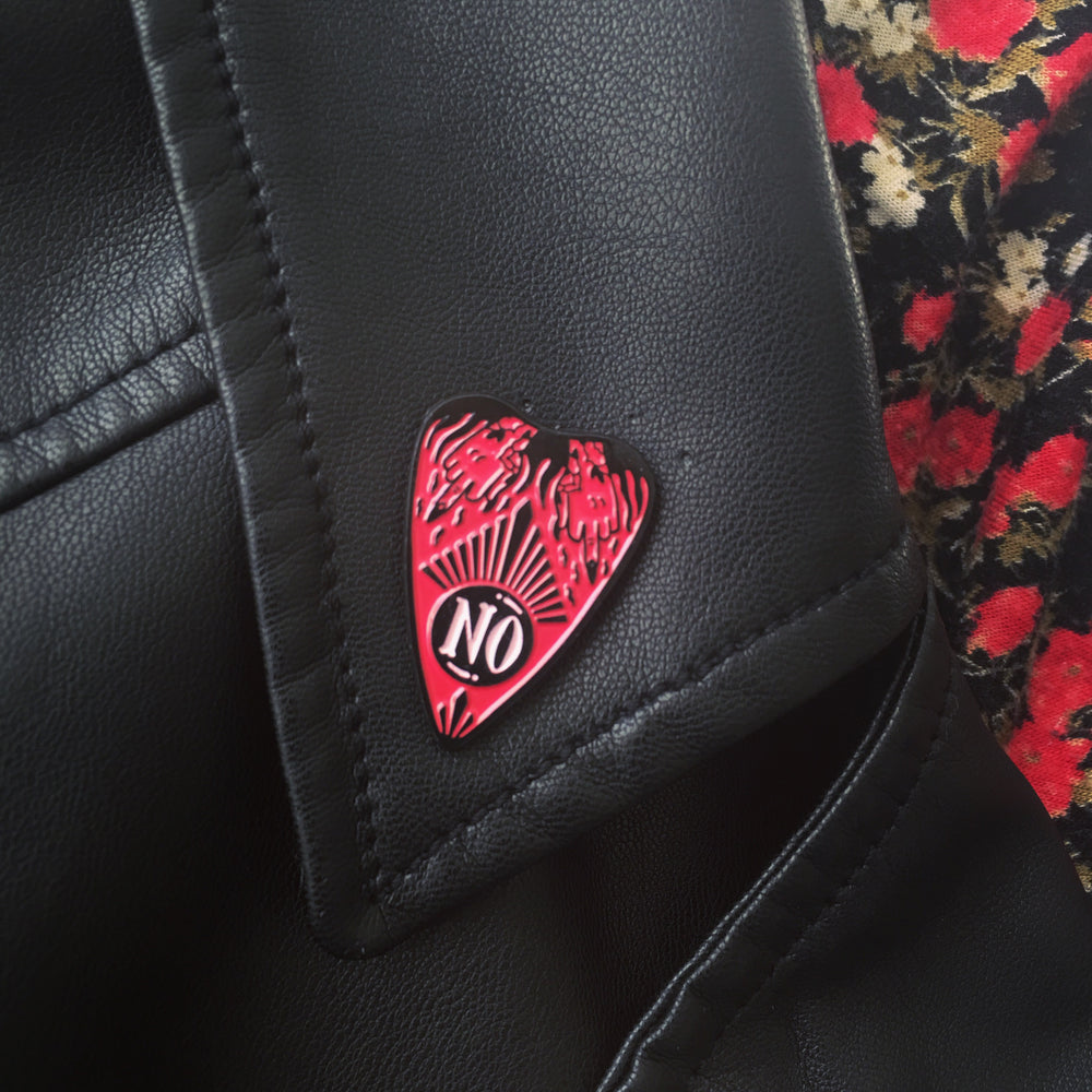 A pink ouija pin shown on the lapel of a leather jacket for womens alternative fashion.
