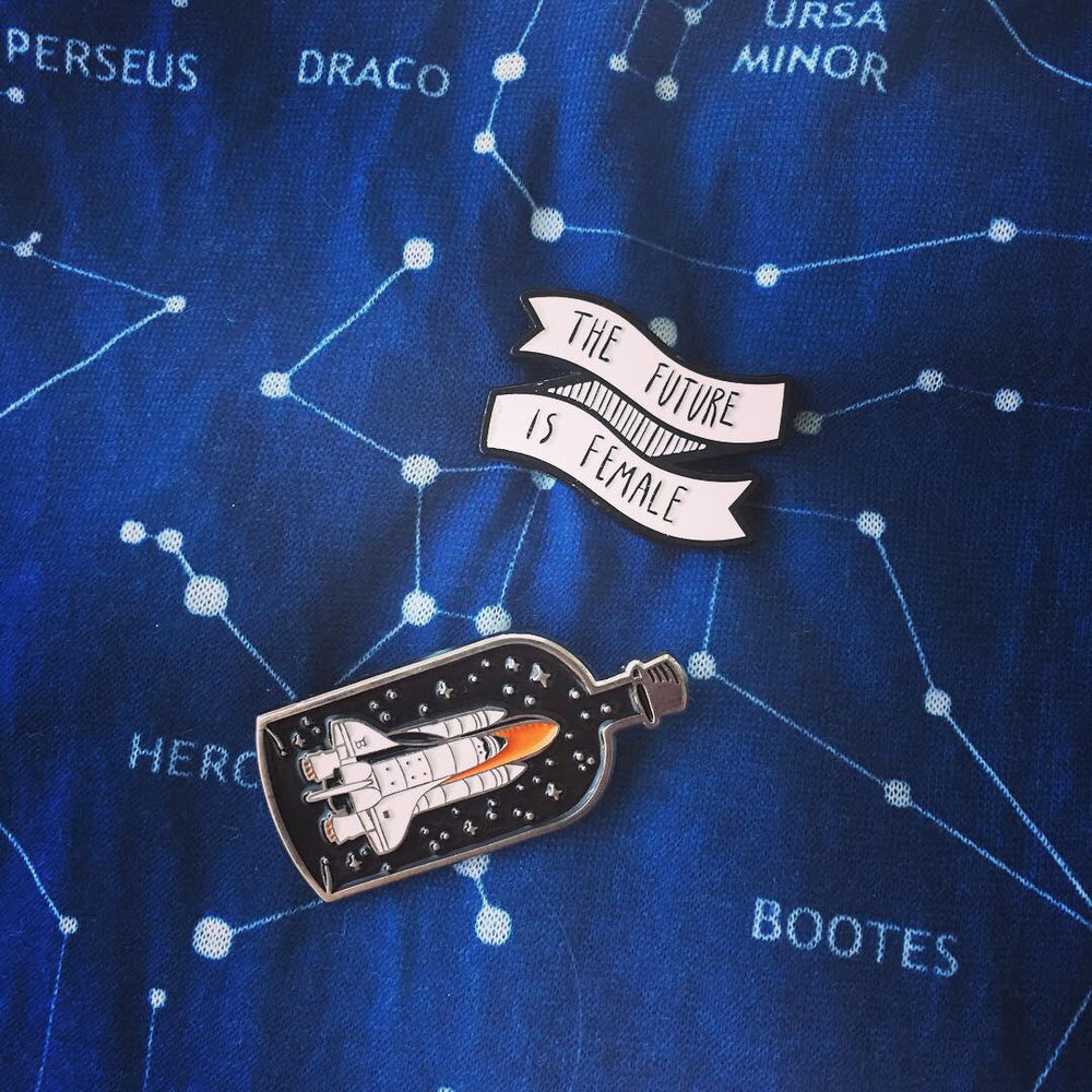 "A cool science themed pin collection of a spaceship and a ""future is female"" pin. Pictured on a starry constellation background."
