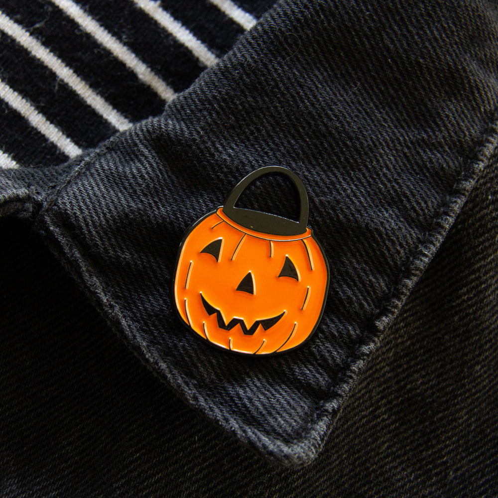 A black and orange vintage inspired brooch on the lapel of a jacket for alternative fashion.