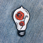 A traditional tattoo inspired enamel pin of a victorian era light bulb with beautiful red roses inside.
