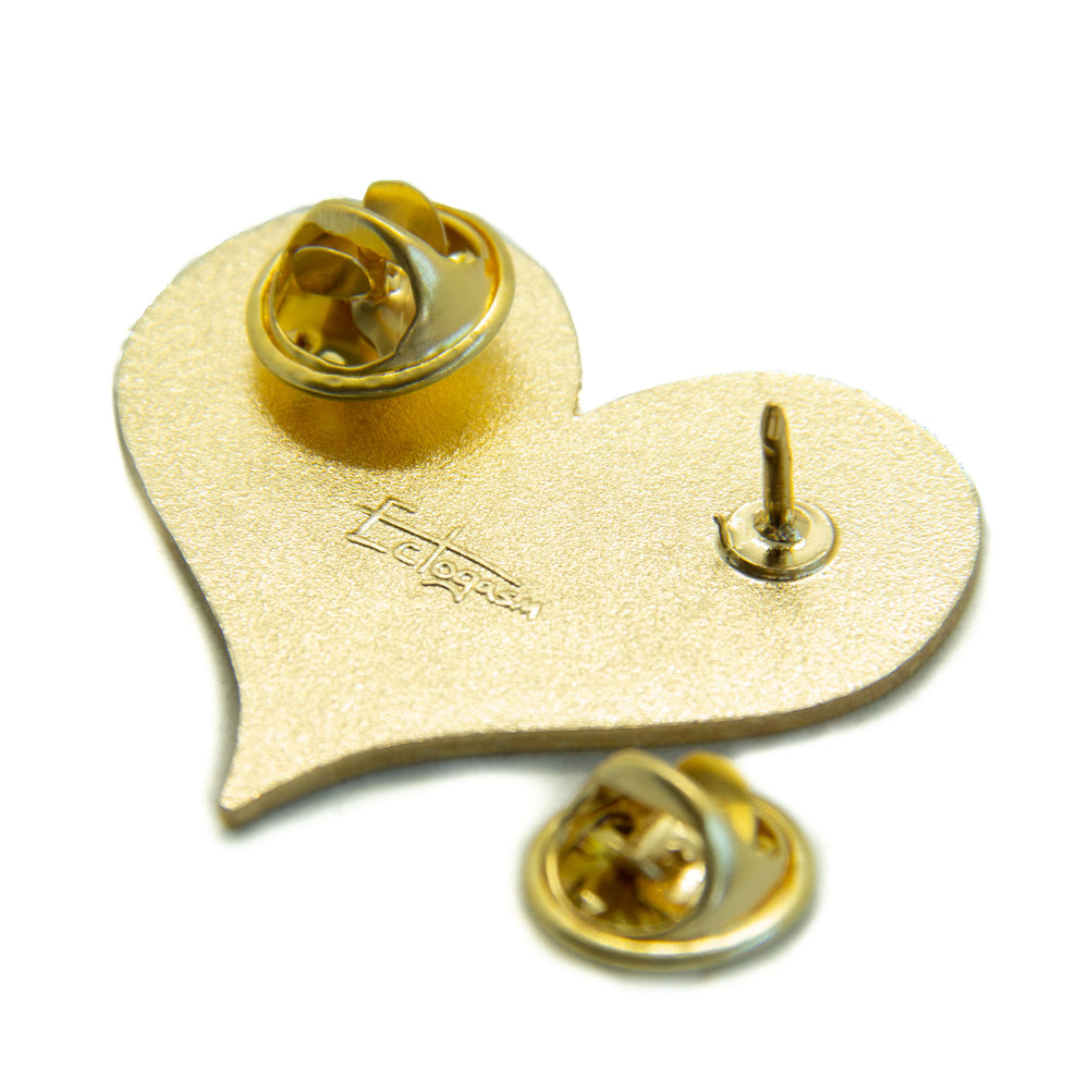 Two metal clasps on the back of a gold Ectogasm enamel pin.