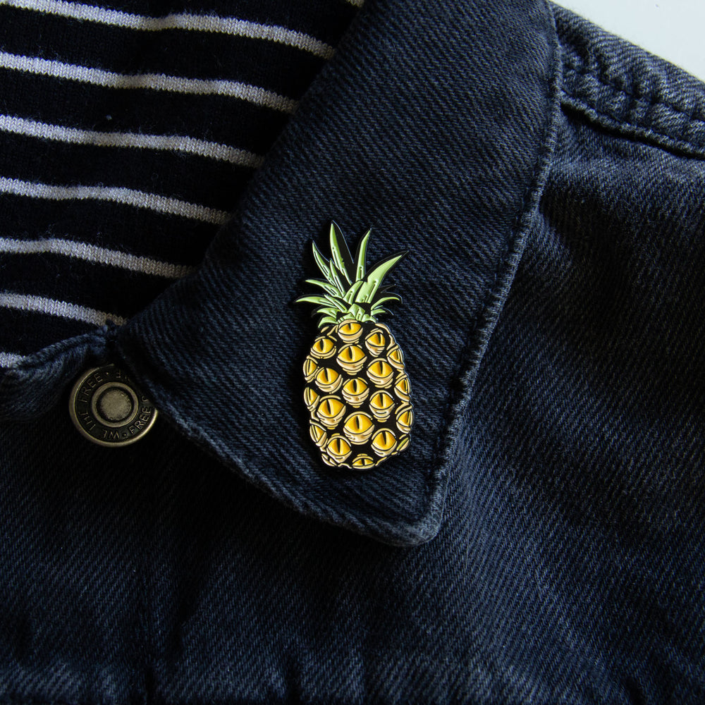A tropical enamel pin of pineapple fruit on the lapel of a men's denim jacket.