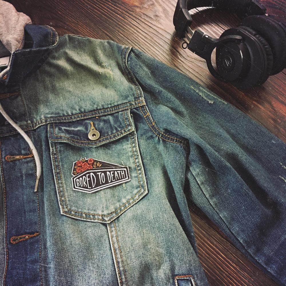 A men's denim jacket with a cool coffin patch for punk rock style.