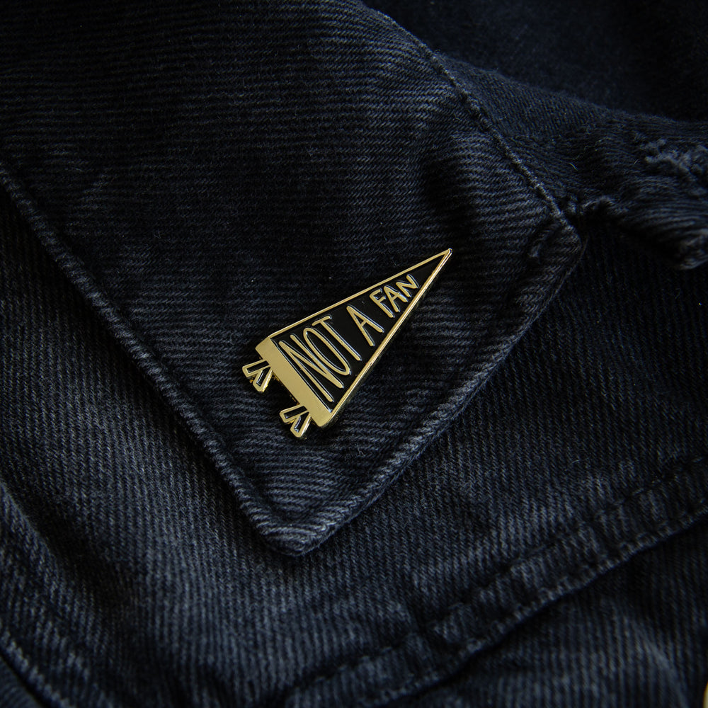 "Ectogasm's ironic ""Not a Fan"" gold flag enamel pin on the lapel of a black denim jacket for unisex fashion."