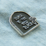 A black and silver enamel pin of a tombstone with a rose and a funny quote for nu goth fashion.