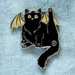 A cute enamel pin of a black cat with demon wings and a pentacle butthole.