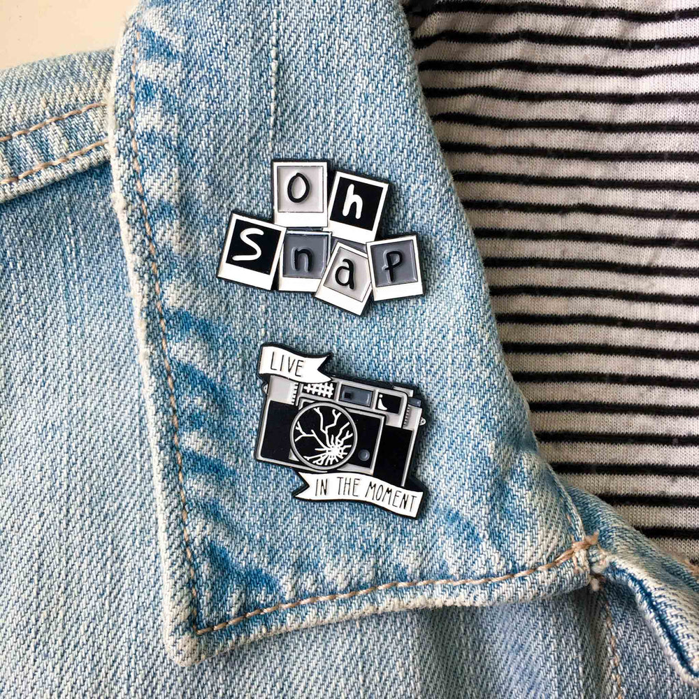 A collection of photography themed enamel pins.