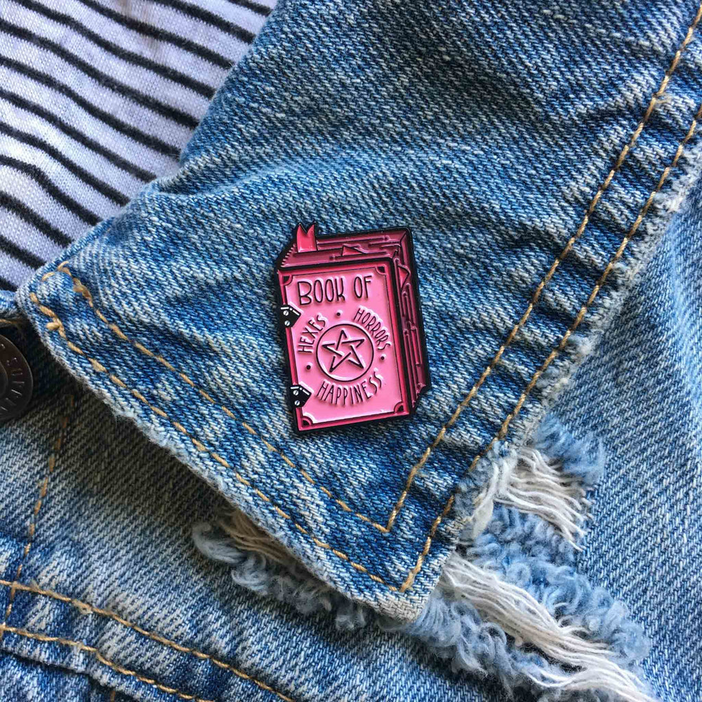 A creepy cute, pink badge of a witch's spell book for pastel goth fashion.