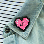 A cute, geek chic lapel pin on a women's jacket.